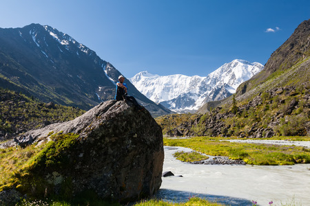 Backpacker rests in green highlands of Altai mountains, Russia