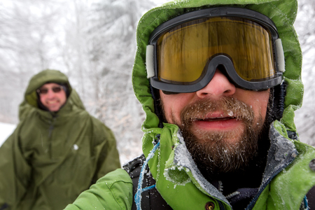 Man is hiking in winter forest on cloudy day Stock Photo
