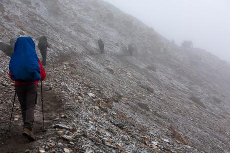 Trekker walking slowly to Thorung La pass - the highest point on Annapurna circuit in Nepal