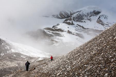 Trekker caminando lentamente a Thorung pase - el punto más alto en el circuito de Annapurna en Nepal Foto de archivo