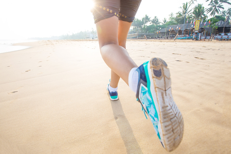 Feet of the woman that is jogging by the sea at the sunrise photo