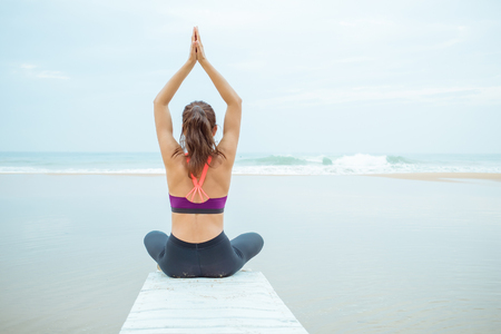 Caucasian woman practicing yoga at seashore on a cloudy day photo