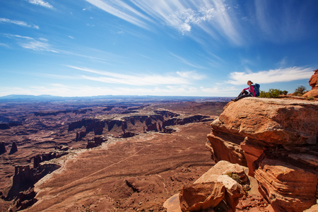 Hiker rests in Canyonlands National park in Utah, USA