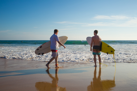 Two men with a surfboard on the beach Stock Photo