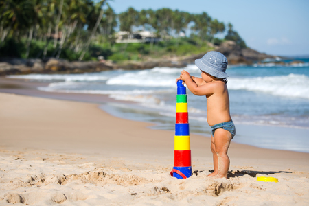 Kid plays with toys at the seashore in summertime