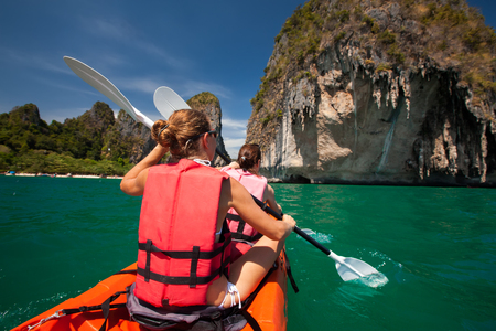 Women are kayaking in the open sea at the Krabi shore, Thailand Imagens - 95033956