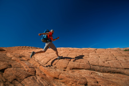 Hiker on a trail in volcanic Snow canyon State Park in Utah, USA Stock Photo