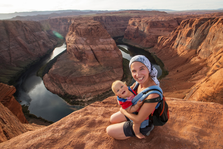 A mother and her baby boy are sitting at the edge of the cliff near Horseshoe band landmark, Arizona, USA