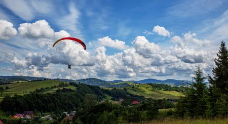 Parapente volando sobre las montañas durante el día de verano Foto de archivo