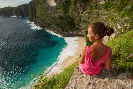 woman sitting on the edge of a cliff and looking at sunset, Nusa Penida