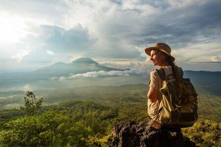 Mujer disfrutando del amanecer desde la cima de la montaña Batur, Bali, Indonesia.