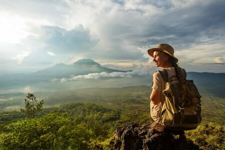 Vrouw genieten van zonsopgang vanaf een top van de berg Batur, Bali, Indonesië.