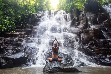 Woman practices yoga near waterfall in Bali, Indonesia Banque d'images - 131858489