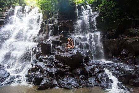 Woman practices yoga near waterfall in Bali, Indonesia Banque d'images - 131858481