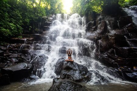 Woman practices yoga near waterfall in Bali, Indonesia Stok Fotoğraf