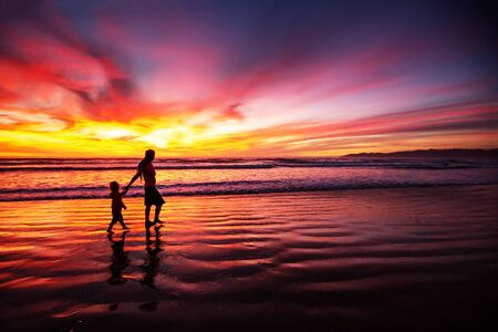 mother and son having fun at sunset on the beach Stock Photo