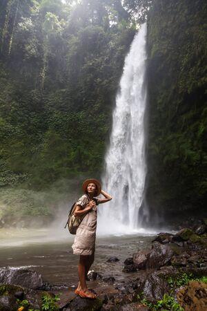 Woman near Nung Nung waterfal on Bali, Indonesia Фото со стока
