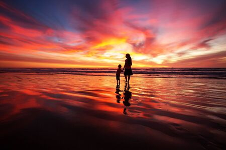 mother and son having fun at sunset on the beach Stock Photo - 131858118