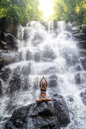 Woman practices yoga near waterfall in Bali, Indonesia Banque d'images - 131858311