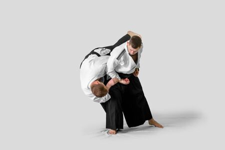 Two caucasian men are practicing aikido on the tatami (isolation path included)