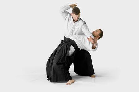 Zwei kaukasische Männer üben Aikido auf der Tatami (Isolationspfad enthalten) Standard-Bild