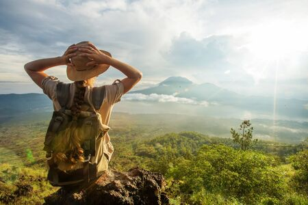 Woman enjoying sunrise from a top of mountain Batur, Bali, Indonesia.  Reklamní fotografie