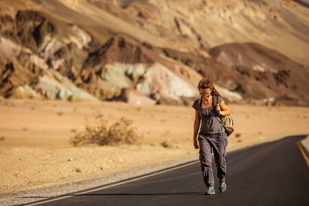 hitchhiker woman walking on a road in USA Stock fotó