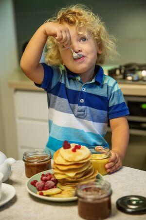 Little curly boy eating sweet pancakes