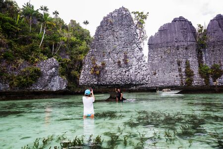 Tourists at the Yapap rock formation, Misool region, Raja Ampat South, Papua, Indonesia