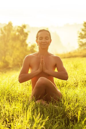 Nude woman practices yoga in nature Stockfoto