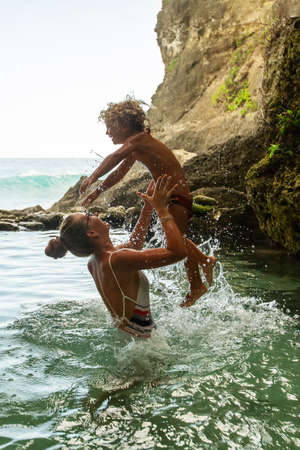 Mom with child in a natural pool by the ocean
