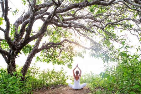 Woman practicing yoga at sunset