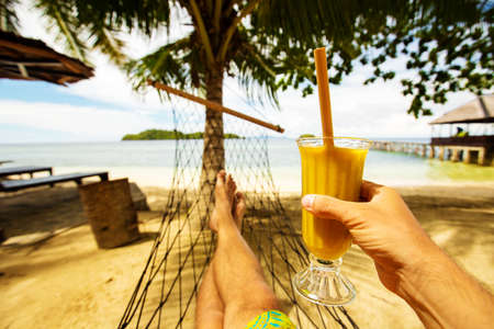 Man drinks mango juice on the beach