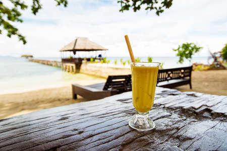 Mango juice on in front of the tropical sea 版權商用圖片