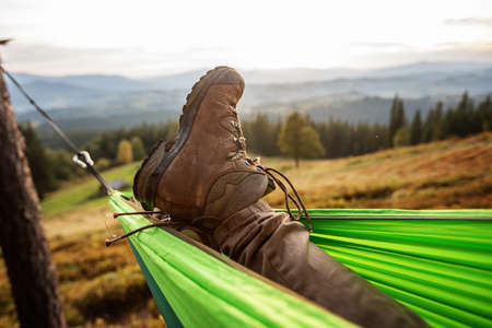 hiker resting after climbing in a hammock at sunset