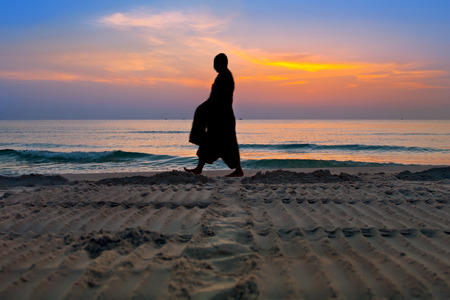 Silhouettes of monks on Hua Hin beach Thailand photo