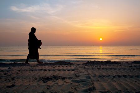 Silhouettes of monks on Hua Hin beach Thailand photo