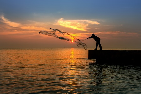a man throwing fishing net during sunset photo
