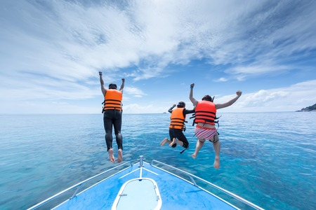 cliff jumping: tree people is jumping from speed boat at Ta-chi, Similan Island, Thailand with happiness Stock Photo