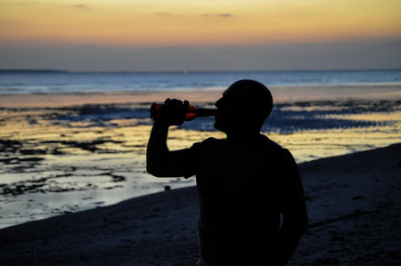 Man drinking a cold beer on a beach at sunset photo