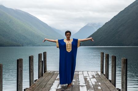 �rabe: mujer de pie con los brazos extendidos en un muelle en el lago de Nelson en Nueva Zelanda