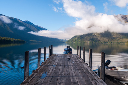 couple in love sitting on the pier at Nelson Lake National Park in the South Island of New Zealand photo