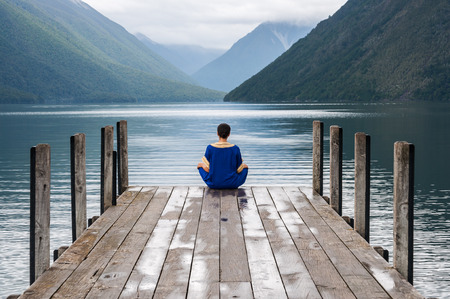 nelson: woman sitting on a pier at Lake Nelson in New Zealand Stock Photo