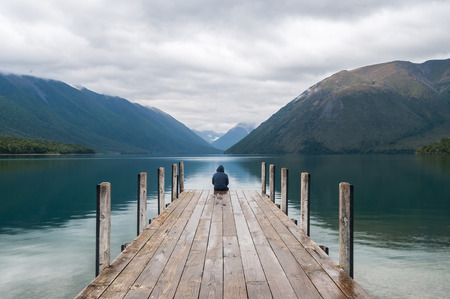 new thinking: man sitting on a pier at Lake Nelson in New Zealand Stock Photo