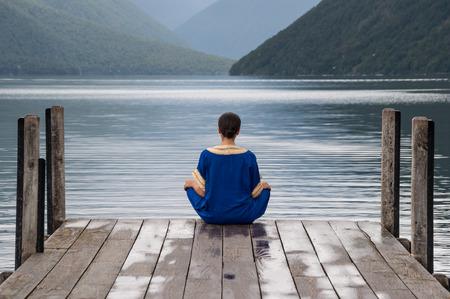 arabe: mujer sentada en un muelle en el lago de Nelson en Nueva Zelanda Foto de archivo