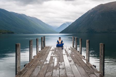 �rabe: mujer sentada en un muelle en el lago de Nelson en Nueva Zelanda Foto de archivo