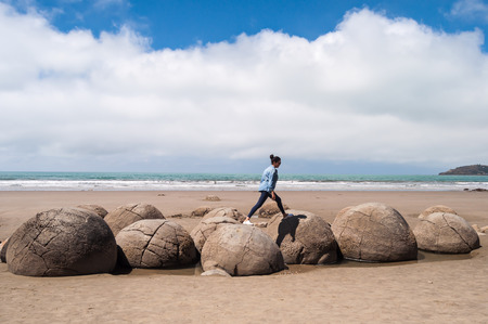 boulders: girl on Moeraki Boulders, New Zealand, spherical geological formations Stock Photo