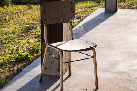 bathed: spider web on an old chair bathed in sunshine
