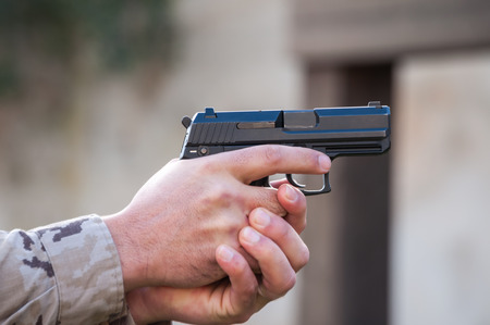 pointing gun: man pointing gun gripped with both hands Stock Photo
