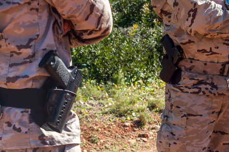 camouflaged: camouflaged soldier in military uniform with gun holstered to his waist